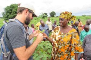 Sam Marshall examining a plant, talking to a local woman