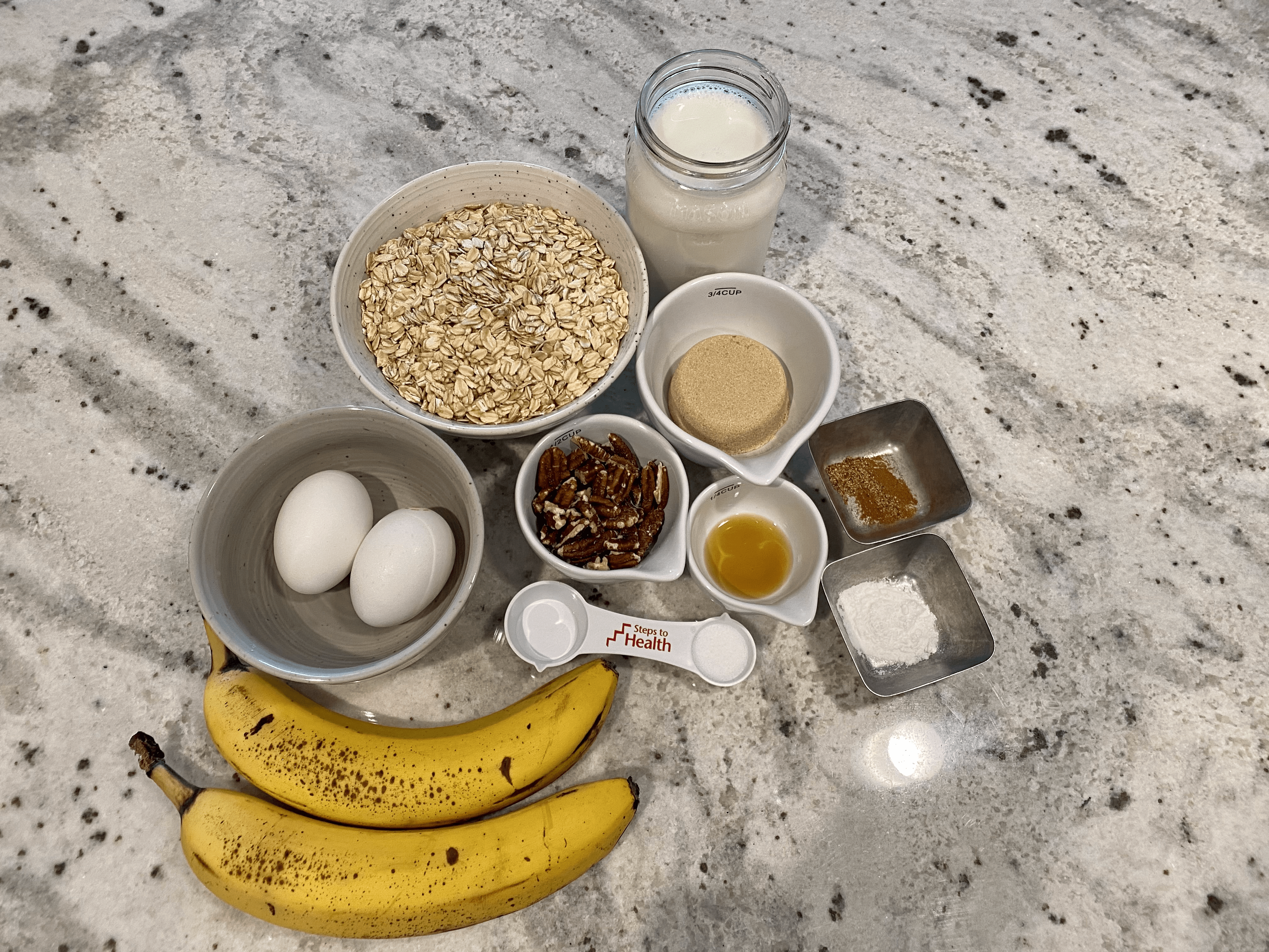 bananas, eggs, tablespoon, and oats on a marble countertop to show ingredients needed to make recipe