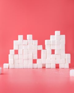 Sugar cubes stacked in front of pink background