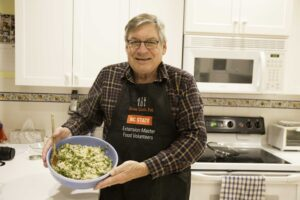 Extension Master Food Volunteer in kitchen wearing apron holding meal he has helped prepare