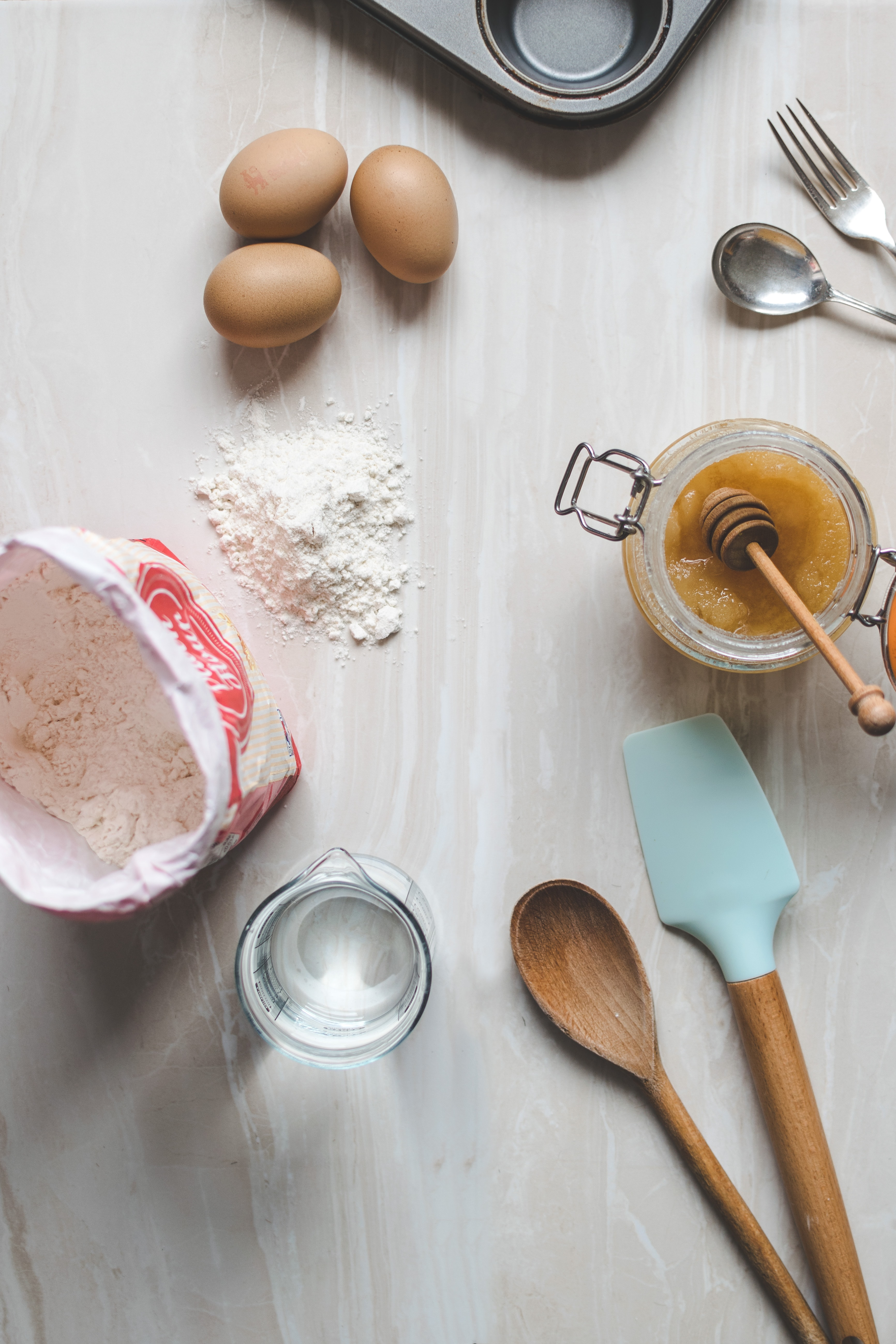 spatulas, flour, eggs, water, pan, and spoon and fork on counter