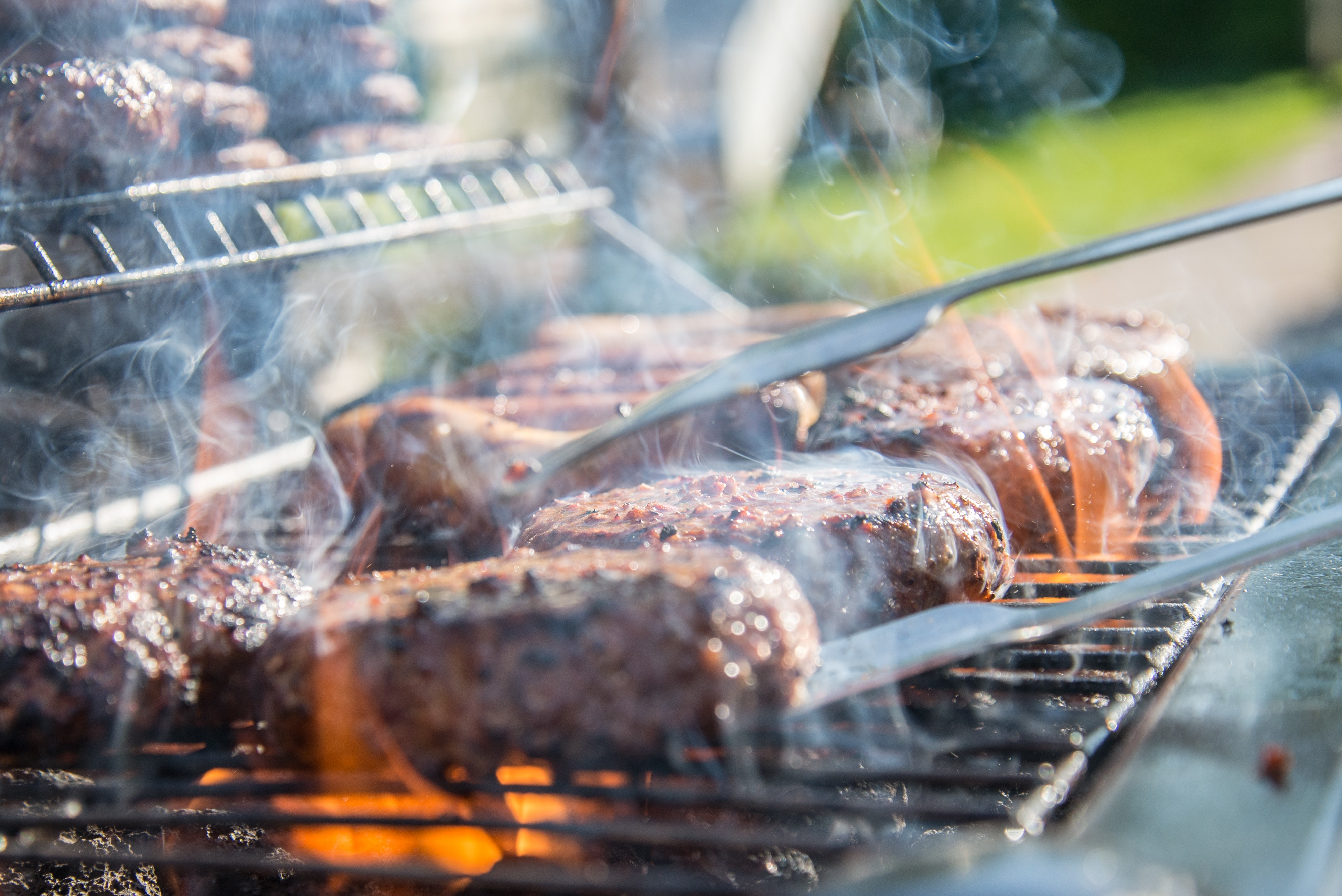 tongs on meet over flame in grill
