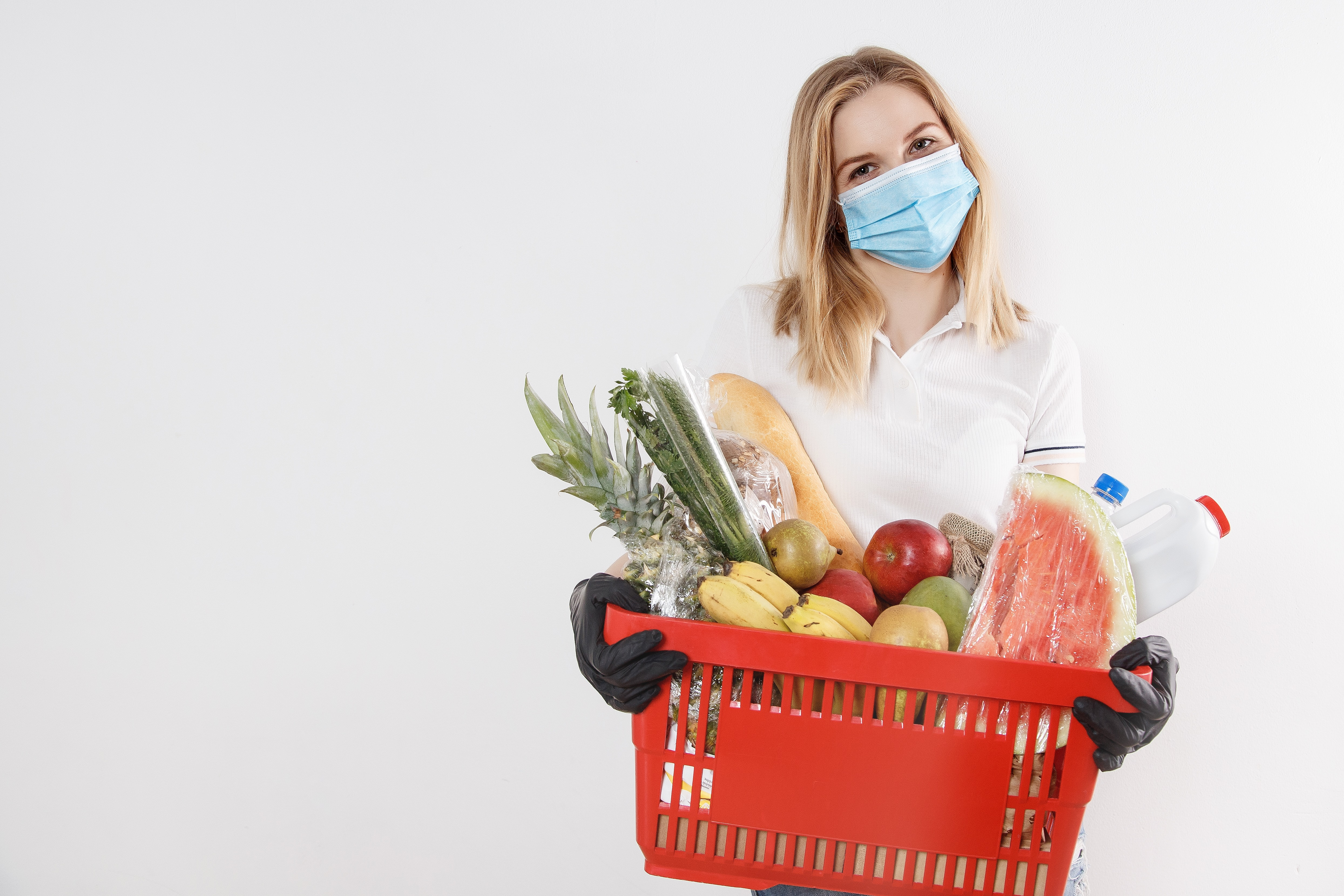 Woman wearing a mask and gloves. Carrying grocery basket with produce.